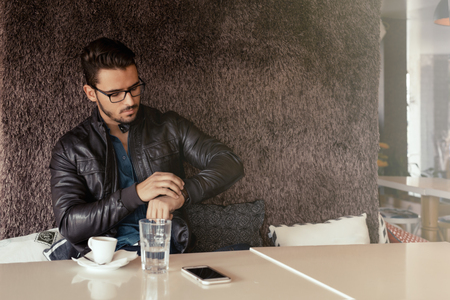 inteligent: Modern businessman looking at his watch while sitting on coffee break