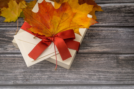 Autumn present box with red ribbon and dry fall leaves decoration