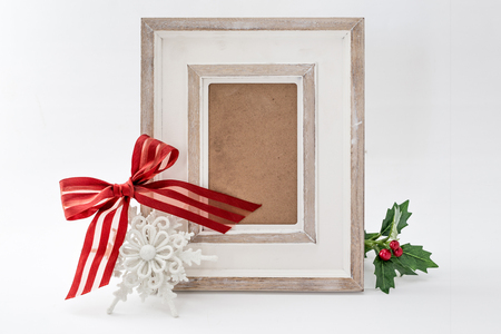 christmas decorations with white background: Closeup of picture frame decorated with red ribbon
