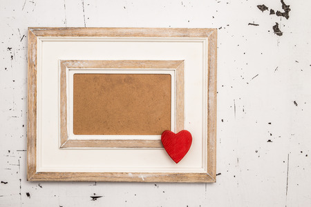 christmas decorations with white background: Closeup of picture frame decorated with red heart figurine