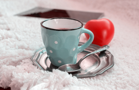 valentine day cup of coffee: Closeup of blue coffee cup on metalic tray on white fur