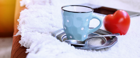 valentine day cup of coffee: Closeup of blue colored coffee cup on tray with red heart Stock Photo