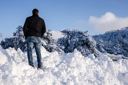 sloping: Back view of male against sloping snowy trees and blue sky background