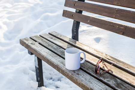 white winter: Alone white teacup on wooden bench in winter park