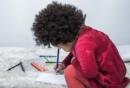 Closeup of curly black kid holding colorful pencil