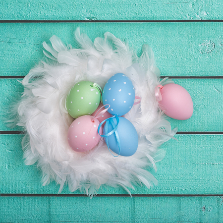 white fur: Easter background of colorful painted eggs and white fur on table