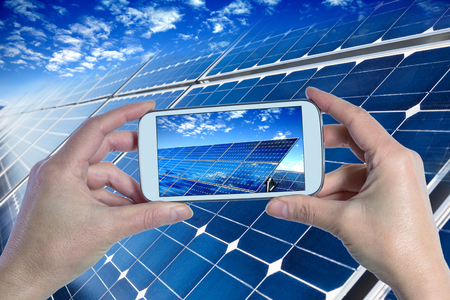 energy picture: Closeup of smartphone showing blue solar panels
