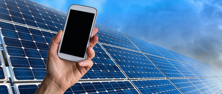 Closeup of human hand holding mobile phone and solar panels