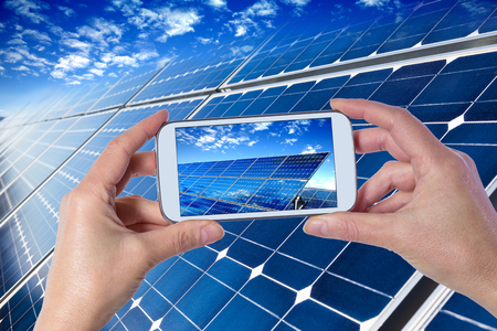 Closeup of hands holding mobile phone showing solar panels Banco de Imagens