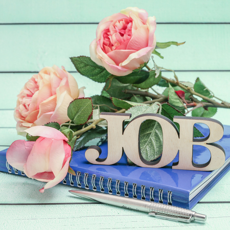 occupancy: Closeup of job text on blue notebook and vintage roses decoration