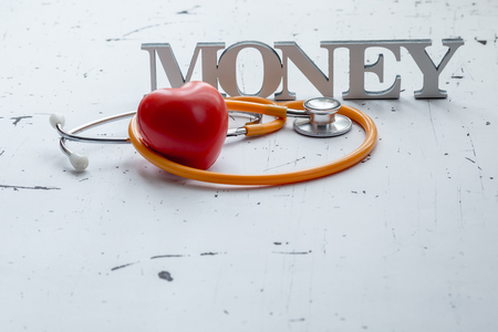 occupancy: Closeup of money word and medical items with red heart Stock Photo