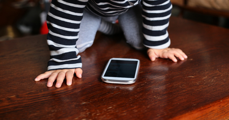 telephonist: Closeup of child hands and white mobile phone