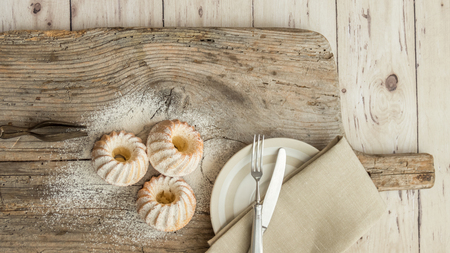 Top view of sweet muffins and white plate on wooden background