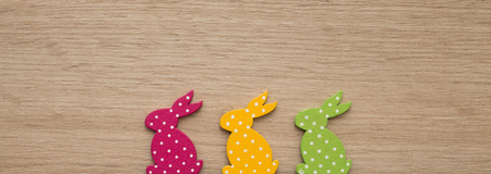 Closeup of easter rabbit figurines over wooden backgorund