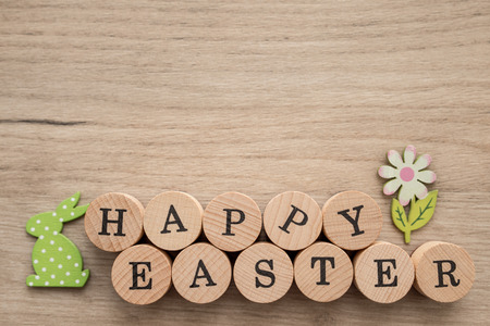 Closeup of happy Easter text with deoctaive figures over wooden background