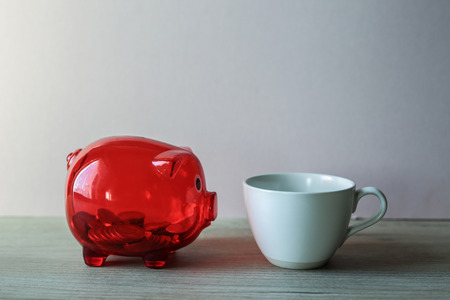 pigling: Closeup of coffee cup and red box with coins
