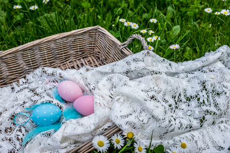 oudoors: Cute painted eggs in basket outside in nature
