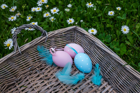 oudoors: Painted easter eggs in wicker basket, closeup shot Stock Photo