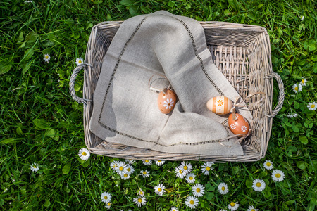 oudoors: Easter background of painted chicken eggs in basket on grass