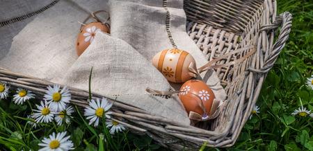 wicker basket: Easter painted eggs in wicker basket on grass