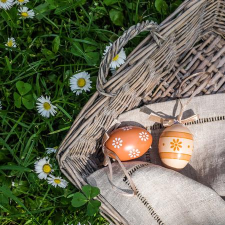 oudoors: Closeup of painted easter eggs in wicker basket against flowers background