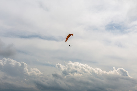 flying man: Flying man with paraplaner in the cloudy sky Stock Photo