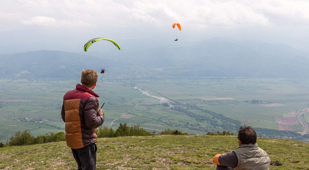 parachutists: Two men observing paragliders in the sky Stock Photo