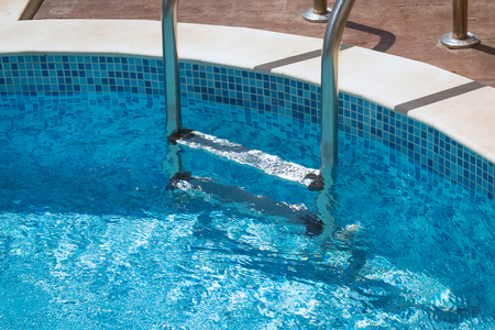leasure: Stairs in the water of the swimming pool Stock Photo