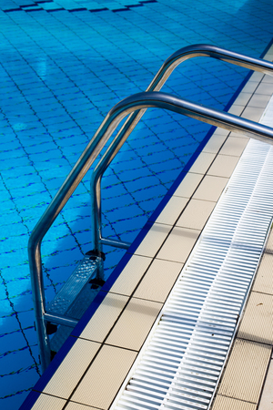metallic stairs: Closeup of stairs leading in the summer pool Stock Photo
