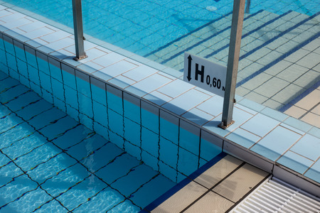 tiled floor: Closeup of swimming pool tiled floor and depth sign