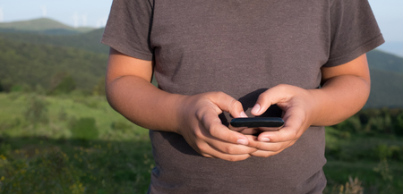 body parts cell phone: Closeup of boy hands holding mobile phone Stock Photo