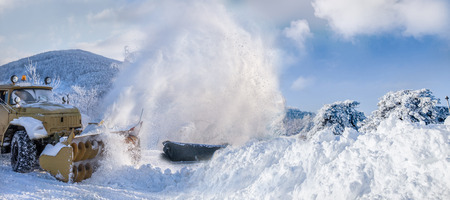 snow plow: Snow plow machine blowing heavy snow while cleaning the road