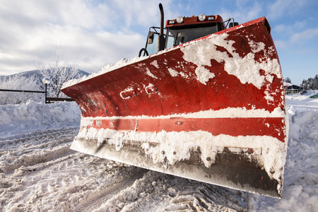 snow plow: Big paddle of snow plow machine on snowy road Stock Photo
