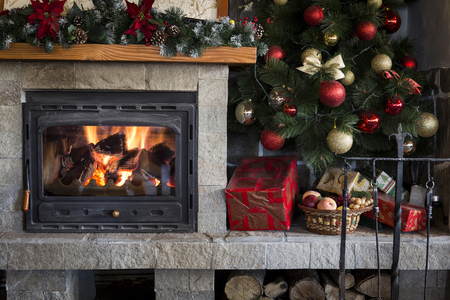fireplace home: Cozy home interior with burning fireplace and colorful christmas decorations