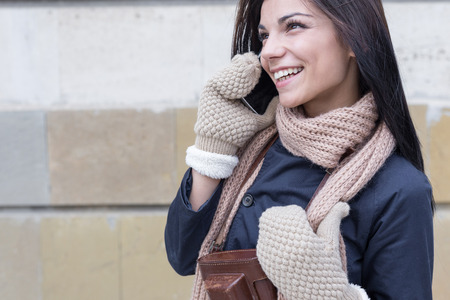 keep in touch: Pretty brunette woman in winter outfit using her phone