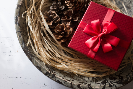 luxurious: Red colored luxurious gift box with pine cones decoration Stock Photo
