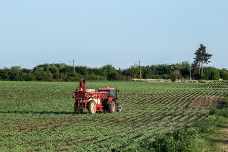 Farmland machine processing fields and blue sky
