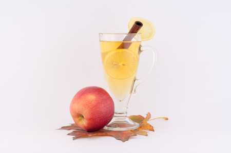 beautiful autumn composition with red apple and tea with cinnamon and lemon on a white background photo