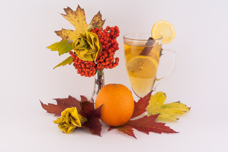 Beautiful decoration made from autumn leaves of roses and tea, orange and cinnamon a white background photo