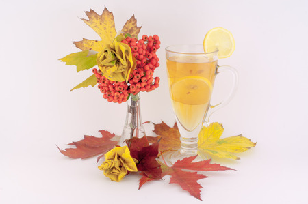 Beautiful decoration made from autumn leaves of roses and tea and lemon a white background photo