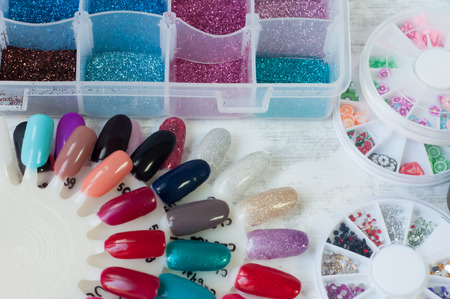 acrylic nails: samples of nail polish and various kinds of decorative elements of decoration Stock Photo