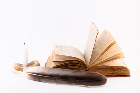 dissolved: vecchie pagine del libro sciolti, candela e penna su uno sfondo bianco