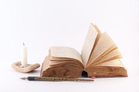 dissolved: pagine del libro disciolti, candela e vecchio penna su uno sfondo bianco Archivio Fotografico
