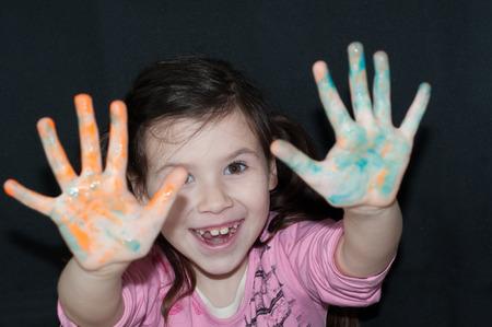 manos sucias: chica con las manos sucias en un fondo oscuro