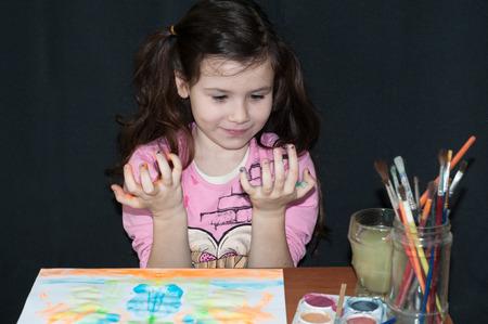 manos sucias: chica con pintura, pinceles y dibujo con las manos sucias en un fondo oscuro