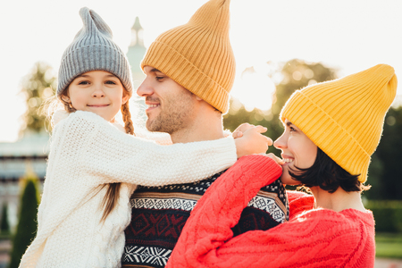 People and relationship concept. Family have unforgettable time together, embrae each other, wear trendy knitted hats. Adorable small girl with pigtails embrace her father, looks happily into camera
