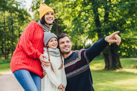 Three family members spend time together, look at beautiful lake in park, indicate with fingers, being in good mood, smile pleasantly. Father, mother and daughter enjoy togetherness, calm atmosphere Stock Photo