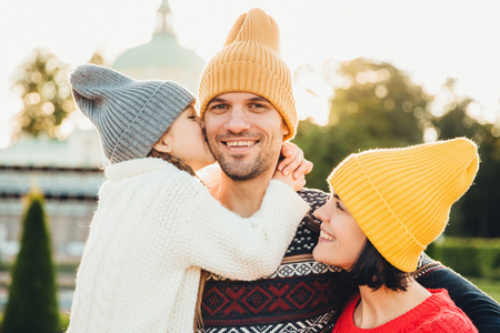 Pleasant looking little girl being thankful to her father for buying new bicycle, kisses him in cheek. Young family walk together outdoor, spend spare time in park, wear knitted fashionable hats
