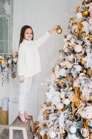 Vertical portrait of female child stands near New Year tree, holds decorated new year ball, decorates fir tree, has happy expression, anticipates miracle. Family, Christmas, holiday, children Banco de Imagens