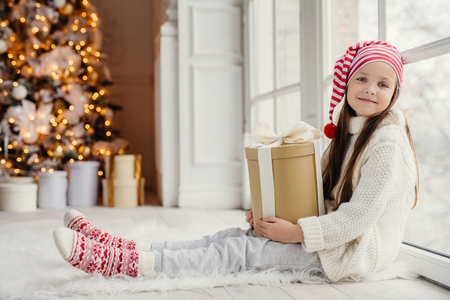 Cute lovely girl with present, sits near window in living room, looks delightfully into camera, admires wonderful beautiful decorated fir tree, has good mood and holidays. New Year concept Stock Photo